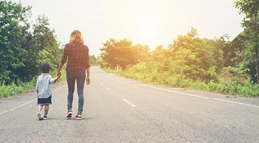 Le emozioni dei bambini: una donna conduce un bambino lungo una strada luminosa