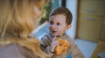 Un bambino mangia insieme alla mamma