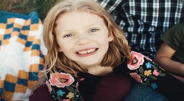 Una bambina sorride mostrando i denti