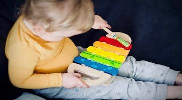 Un bambino sperimenta la musica giocando uno strumento