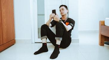 Un ragazzo solo in una stanza con uno smartphone